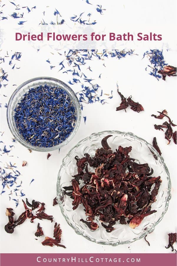 Dried flowers add colour to DIY aromatherapy bath salt and turn this herbal bath salts recipe into a true wellness experience and elegant skincare treat. Any type of dried flowers will look beautiful, I chose bright blue cornflower petals and fragrant red hibiscus. The flowers add a natural floral scent to the detox bath salts and steeping dried flowers in warm bath water is beneficial for your skin and body. #driedflowers #floralbathsalts #herbalbathsalts #herbalism | countryhillcottage.com