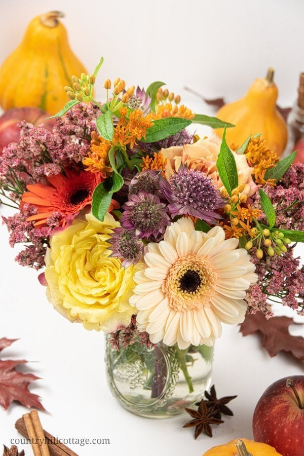 A bountiful autumn bouquet is not only a pretty sight and lovely piece of DIY fall home décor, the florals also provide natural fall scents. To make an easy autumn flower arrangement, grab a few roses, gerbera daisies, and other flowers, trim the stems and put the bouquet into a mason jar. Pretty and wonderfully fragrant! #homedecor #autumn #fall #flowers #bouquet #roses #masonjar #gerbera| countryhillcottage.com